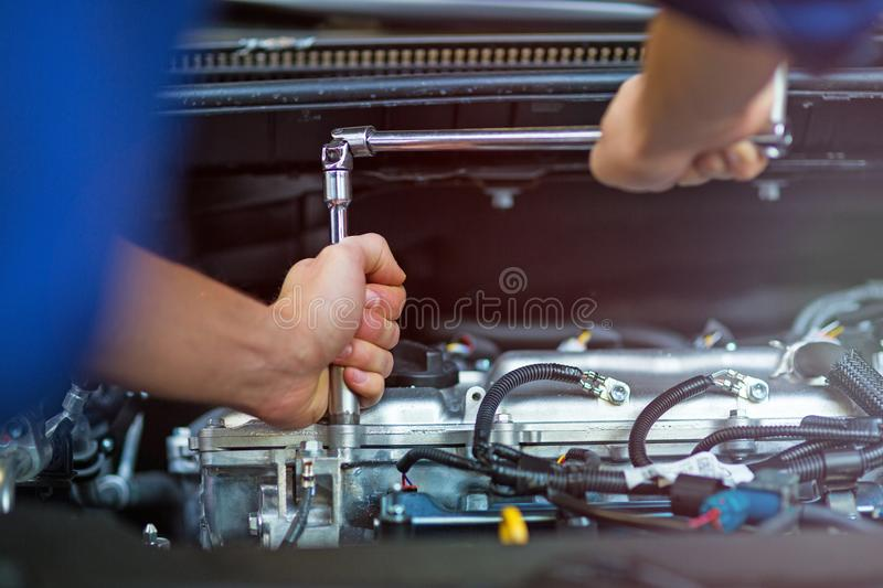 Mechanic working on car engine in auto repair shop. Hands of mechanic working on car engine in auto repair shop royalty free stock photos