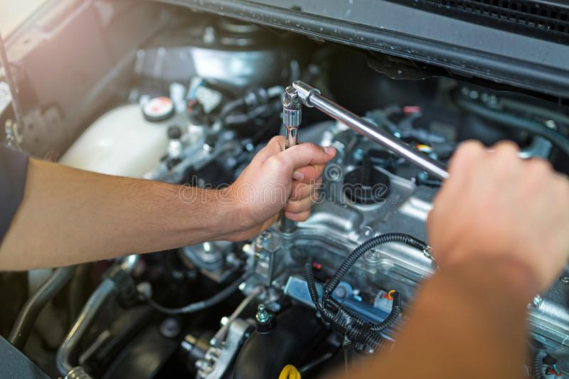 Mechanic working on car engine in auto repair shop. Hands of mechanic working on car engine in auto repair shop royalty free stock images