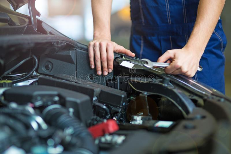 Mechanic working on car engine in auto repair shop. Hands of mechanic working on car engine in auto repair shop royalty free stock photo