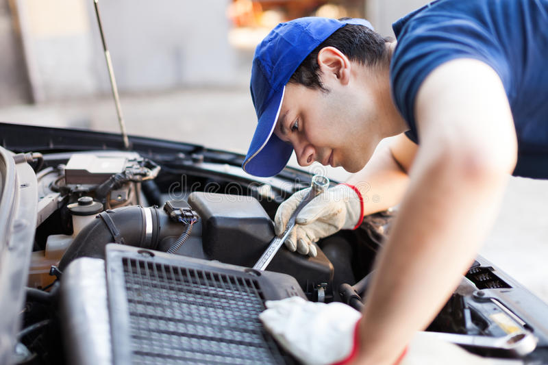 Mechanic working on a car engine royalty free stock photo