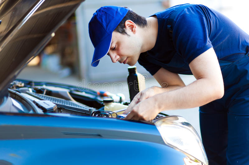 Mechanic working on a car engine royalty free stock image