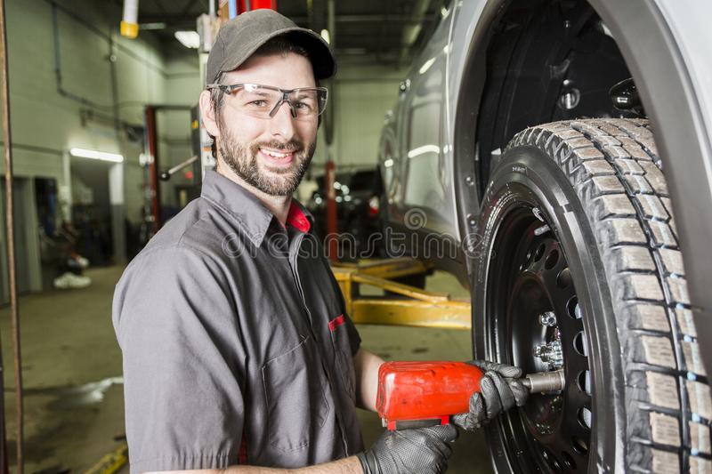 Mechanic working on car in his shop. A Mechanic working on car in his shop royalty free stock photo