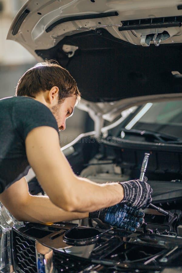 Mechanic working under car hood in repair garage. Mechanic working in car hood in garage stock image