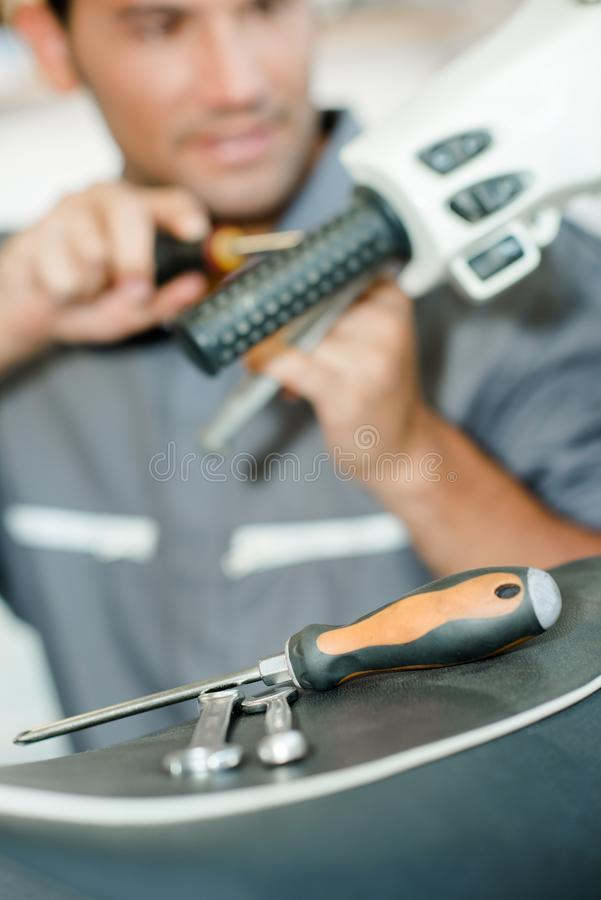 Download Mechanic Working On Handlebars Scooter Stock Photo - Image: 101434122