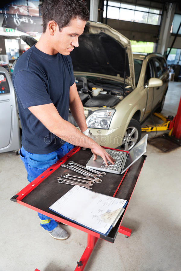 Mechanic working on laptop. Serious looking mechanic working on a laptop in garage stock photo