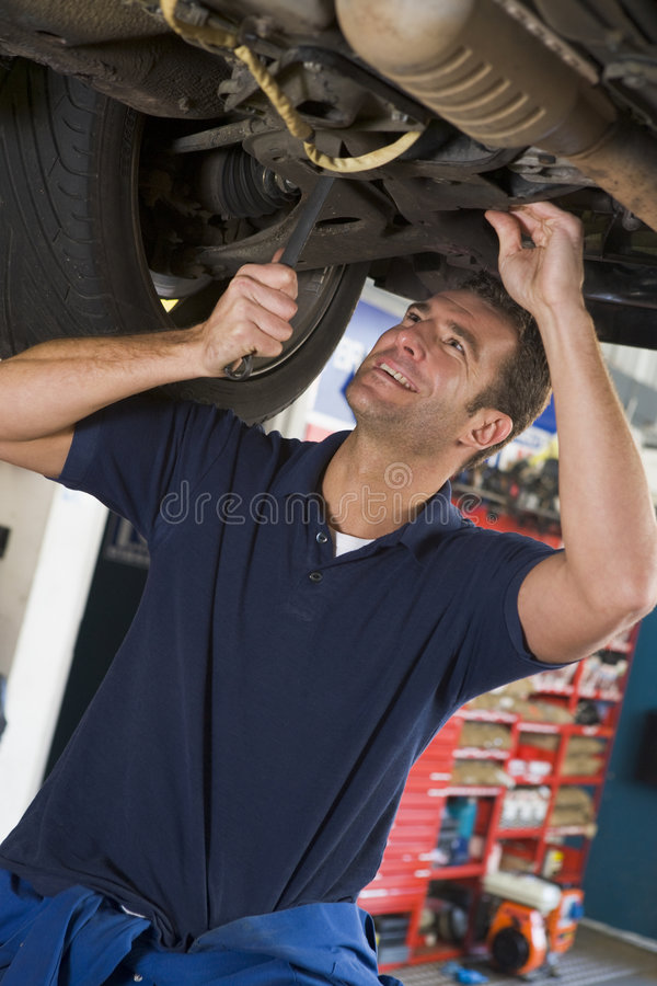 Mechanic working under car. Smiling royalty free stock images