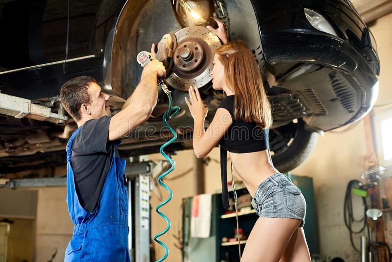 Mechanic works with an automatic screwdriver to fix the steering mechanism stock images