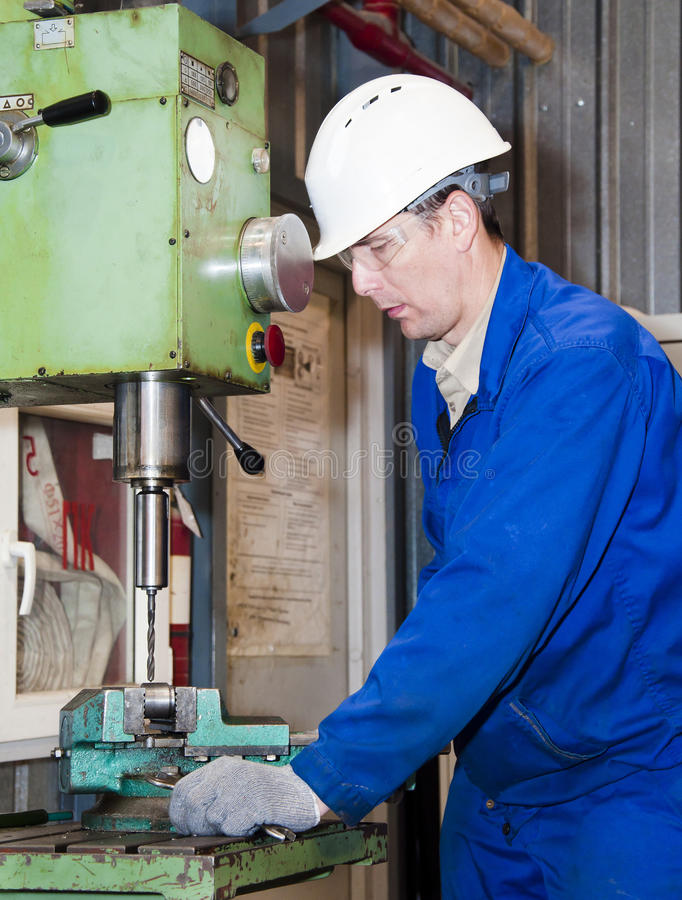 The mechanic works at the machine. The mechanic dressed in overalls, works at the boring machine royalty free stock photos