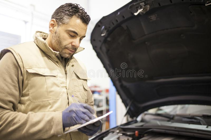The mechanic works in the workshop stock images