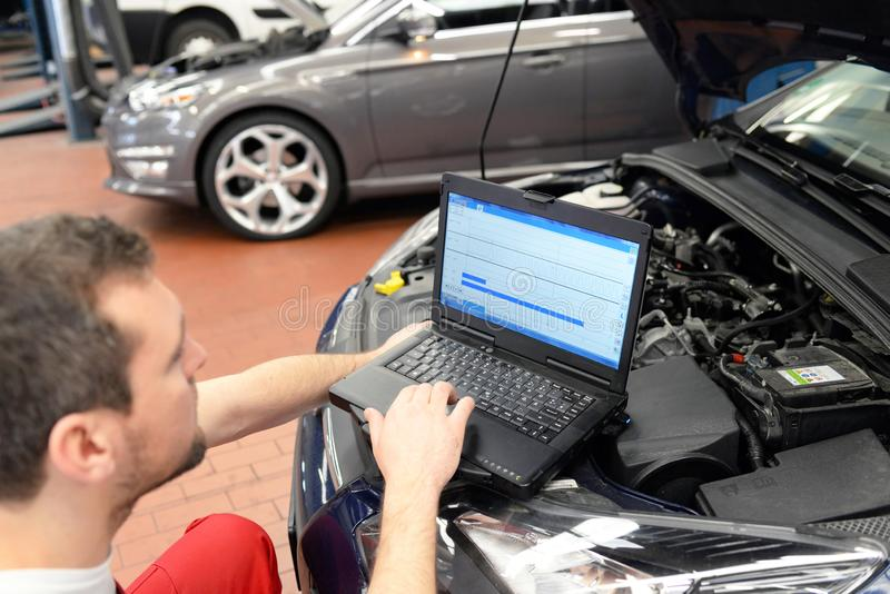 Mechanic in a workshop checks and checks the electronics of the car - software update with a modern computer. Closeup photo stock image
