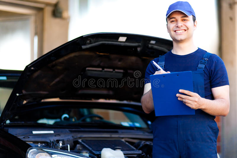 Mechanic writing on clipboard royalty free stock images