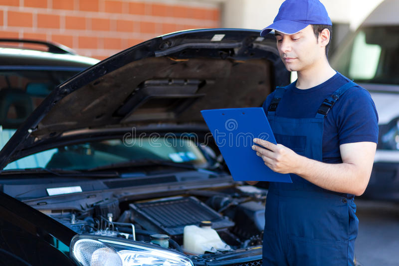 Mechanic writing on a clipboard stock images