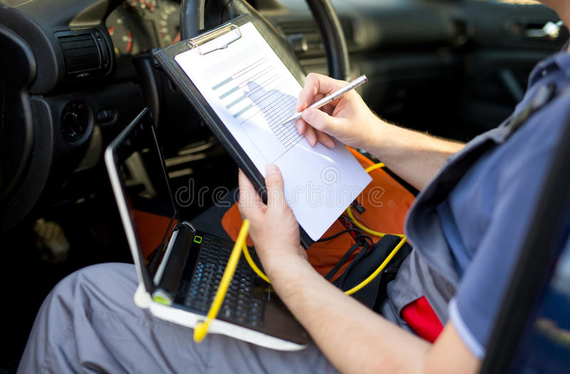 Mechanic writing on clipboard, sitting in the car, close up stock images