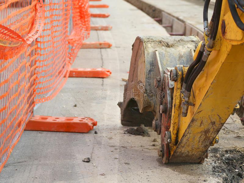 Mechanical arm of the excavator digging on the road. During the work of laying an optical fiber royalty free stock image