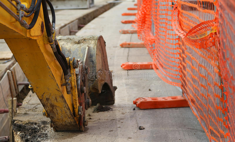 Mechanical arm of the excavator digging on the road. Excavator digging on the road during the work of laying an optical fiber royalty free stock photo