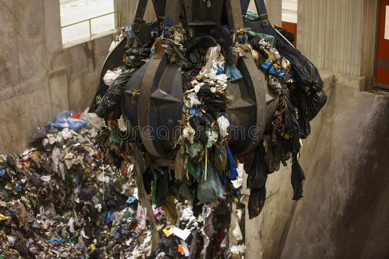 Mechanical claw hand grabbing pile of mixed waste royalty free stock image