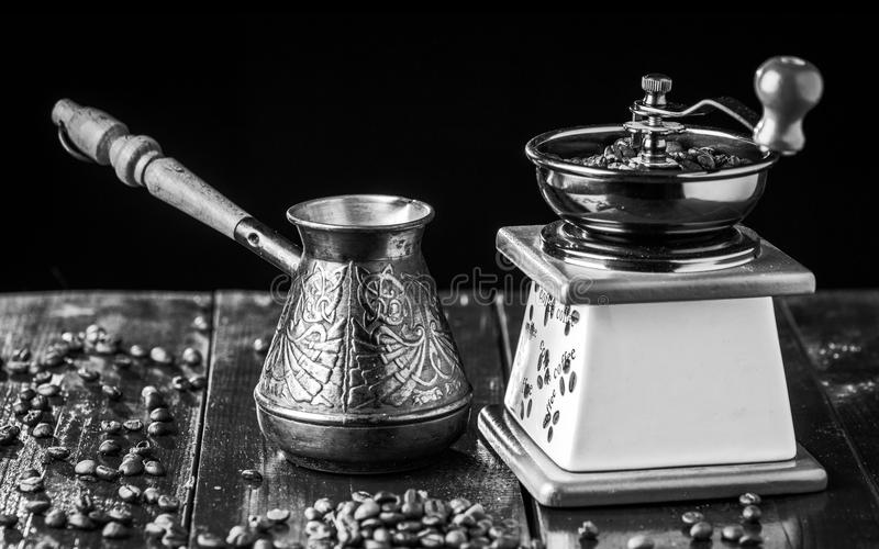 Mechanical coffee grinder, old copper cezve and coffee beans. Black and white. royalty free stock photos
