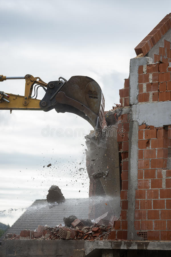 Mechanical digger demolishing a building. Bucket of a backhoe or mechanical digger against the skyline demolishing the wall of a brick building with flying stock images