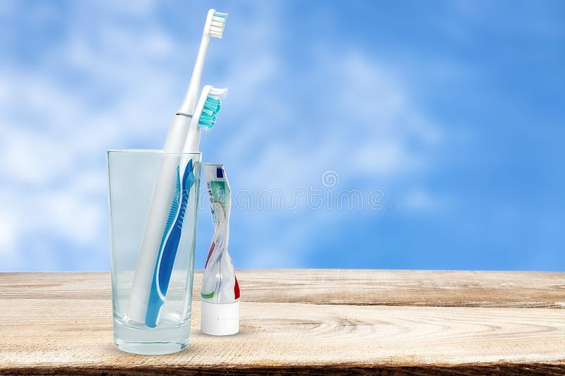Mechanical and electric toothbrushes on sky background stock images