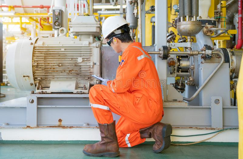 Mechanical engineer checking electric motor and centrifugal pump system at offshore oil and gas central processing platform. royalty free stock photography