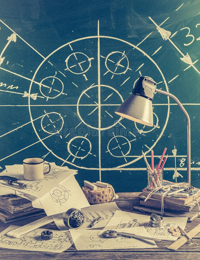 Mechanical engineer desk at the school on green chalkboard background royalty free stock photo