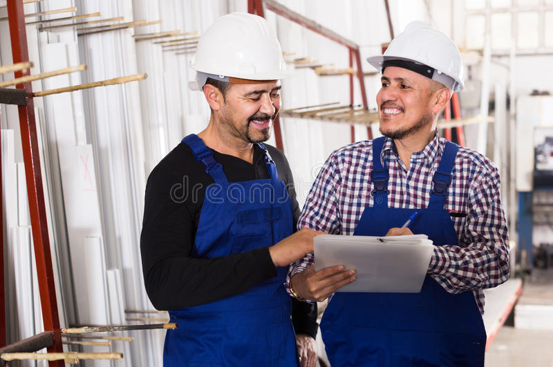Mechanical engineer inspecting the work of labour at factory. Positive russian mechanical engineer inspecting the work of labour at modern factory royalty free stock photos