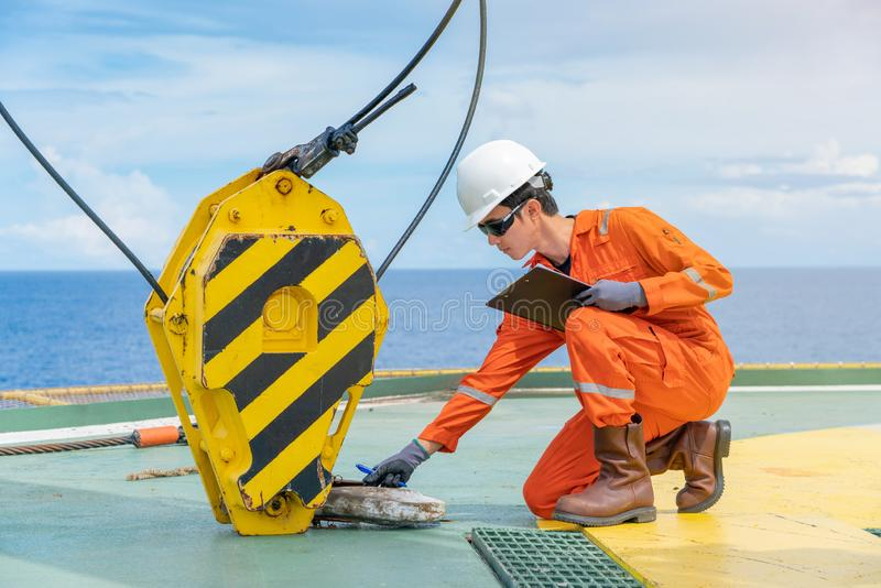 Mechanical engineer inspector is inspecting, testing lifting equipment of pedestal crane on offshore oil and gas wellhead remote stock photos