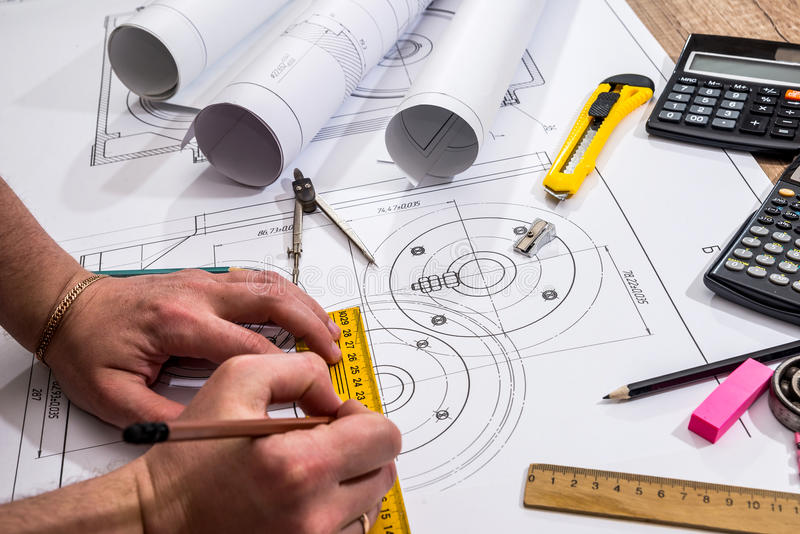 Mechanical engineer with work at technical drawings. And work tools royalty free stock images