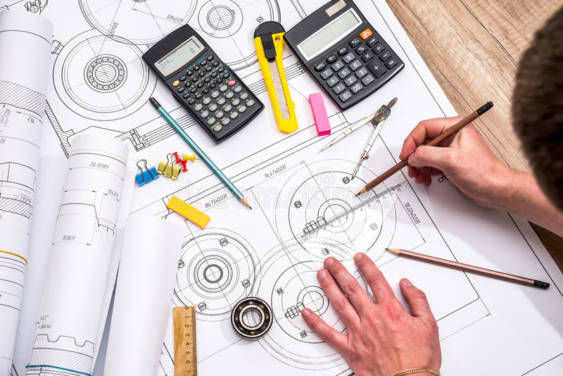 Mechanical engineer with work at technical drawings. And work tools stock photography