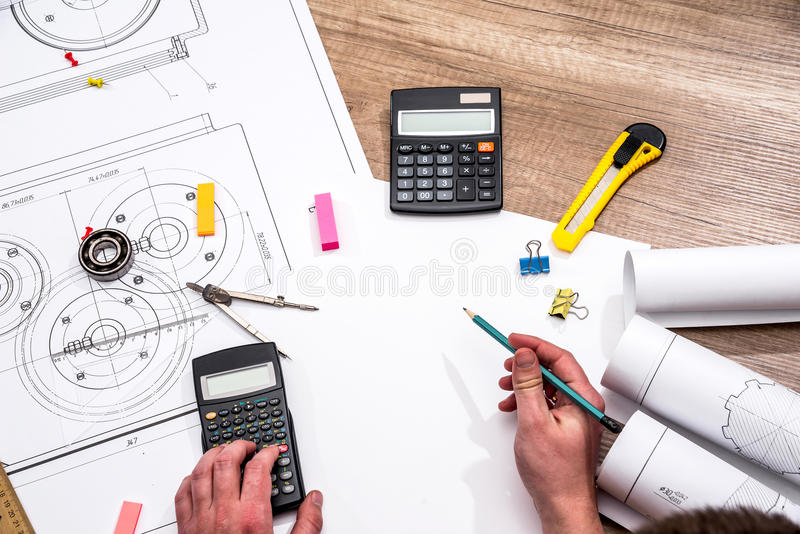 Mechanical engineer with work at technical drawings. And work tools royalty free stock image