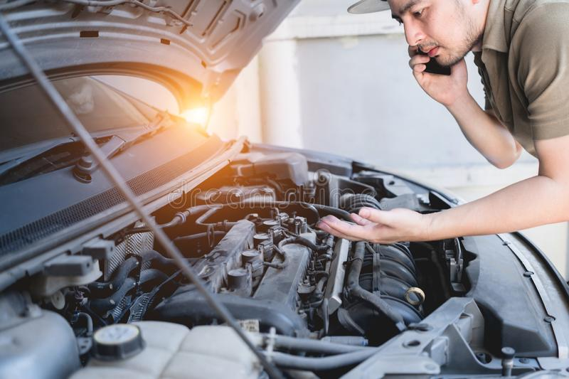 Mechanical fixing car at home. Repairing Service advice by mobile phone. Mechanic, technician man checking car engine. Car service royalty free stock photo