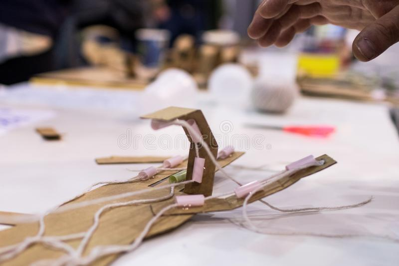 Mechanical hand of cardboard for children built during STEM activities in the classroom..Human hand and mechanical hand in contra stock photos