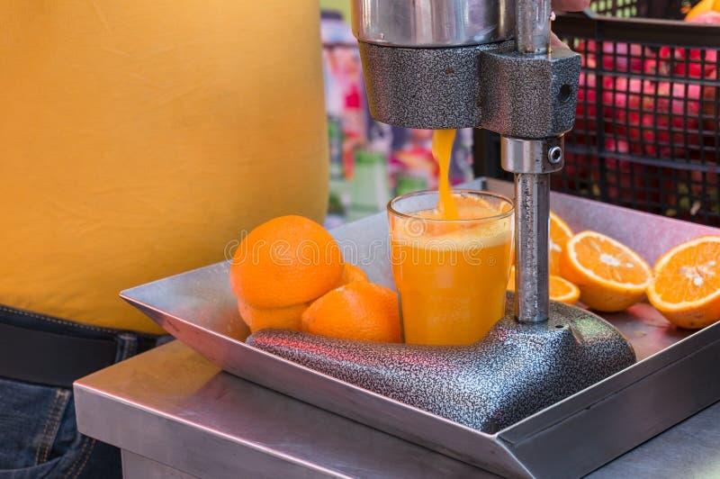 Mechanical juice press. Making orange juice using squeezing machine royalty free stock photo