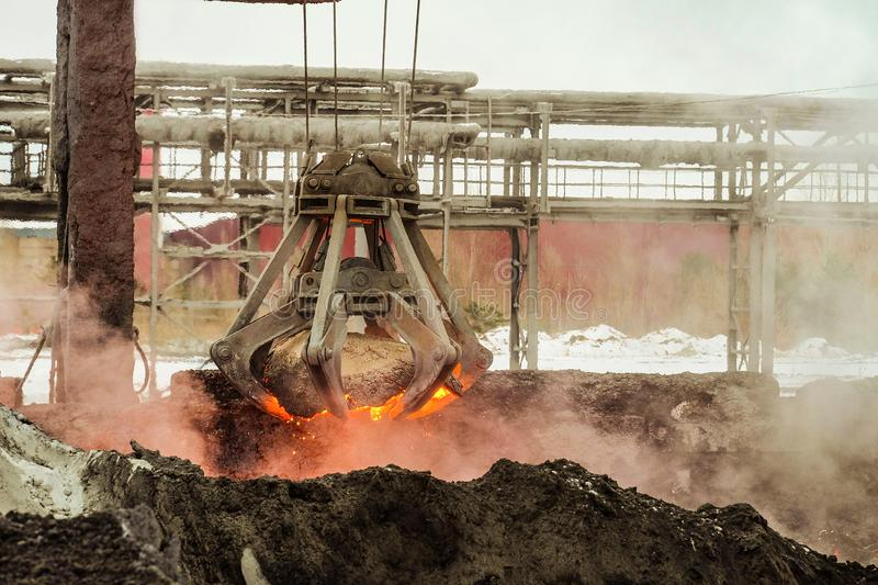 Mechanical multivalve clamshell grapple transports of red-hot piece of iron from the melt on a background evaporation of molten ir. On and slag. Metallyrgical stock images