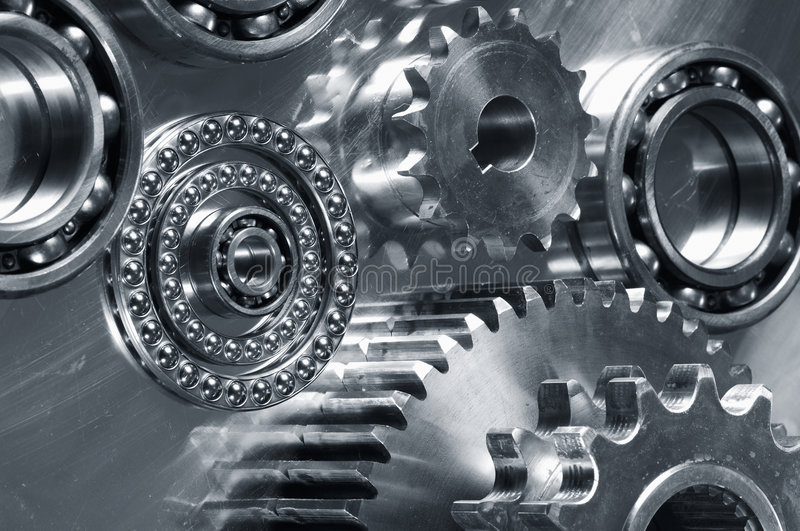 Mechanical parts study. Gears and bearings on display in a dark duplex metallic blue toning royalty free stock photos