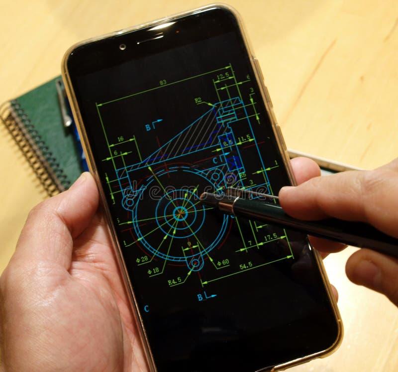 Mechanical piece scheme. Engineer working on mechanical piece scheme on mobile device royalty free stock photo