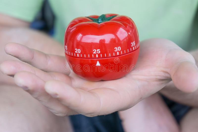 Mechanical red tomato kitchen timer set to 25, held by one open hand stock images