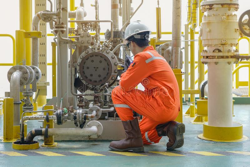 Mechanical specialist check oil pump centrifugal type and use walkie talkie talk to central control room to function test pump. Offshore oil and gas industry stock photo