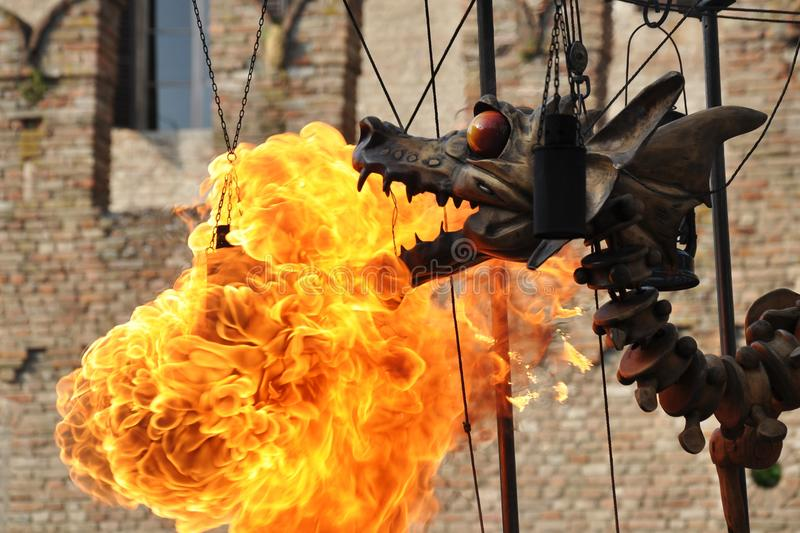 Mechanical steel steampunk-like dragon emit fire. Mechanical steel steampunk styled dragon driven with chains and steel ropes emit fire stock photography