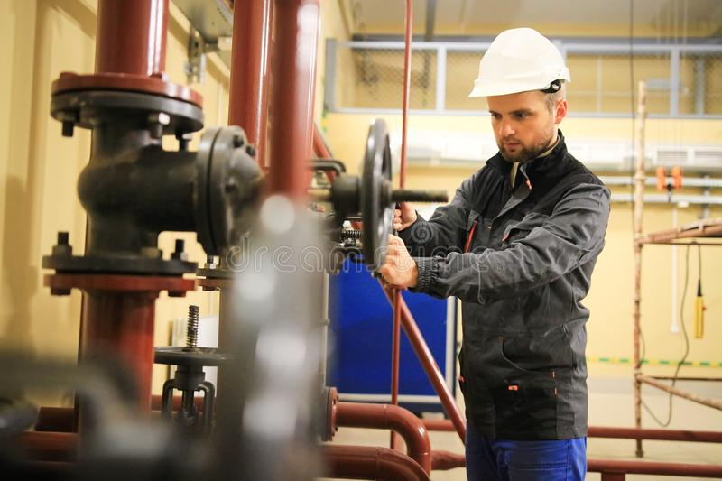 Mechanical worker closes gate valve of pipeline in gas and oil industrial factory. royalty free stock image