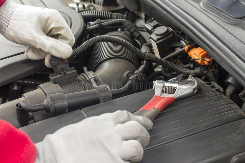 Mechanician, der Wartung auf einem Automotor durchführt stockfotos