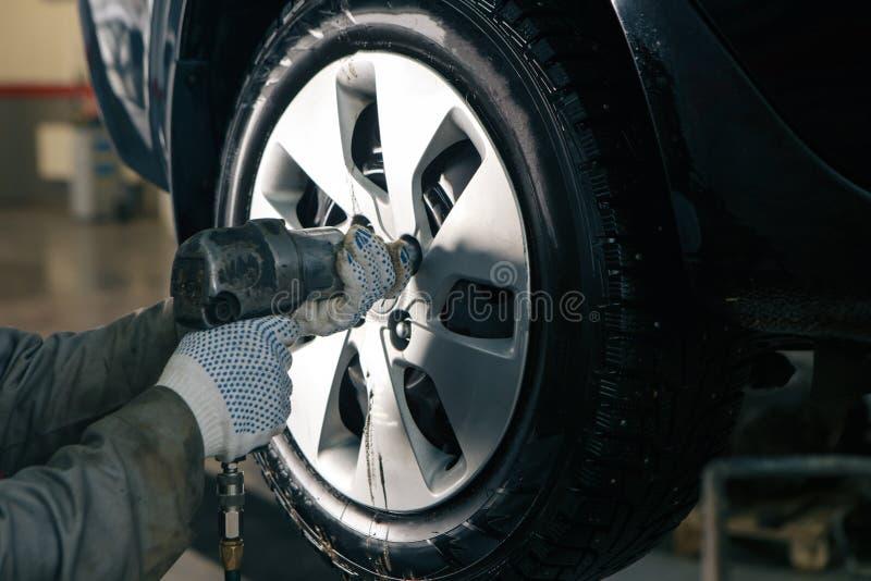 Mechanician veranderend autowiel in autoreparatiewerkplaats stock fotografie