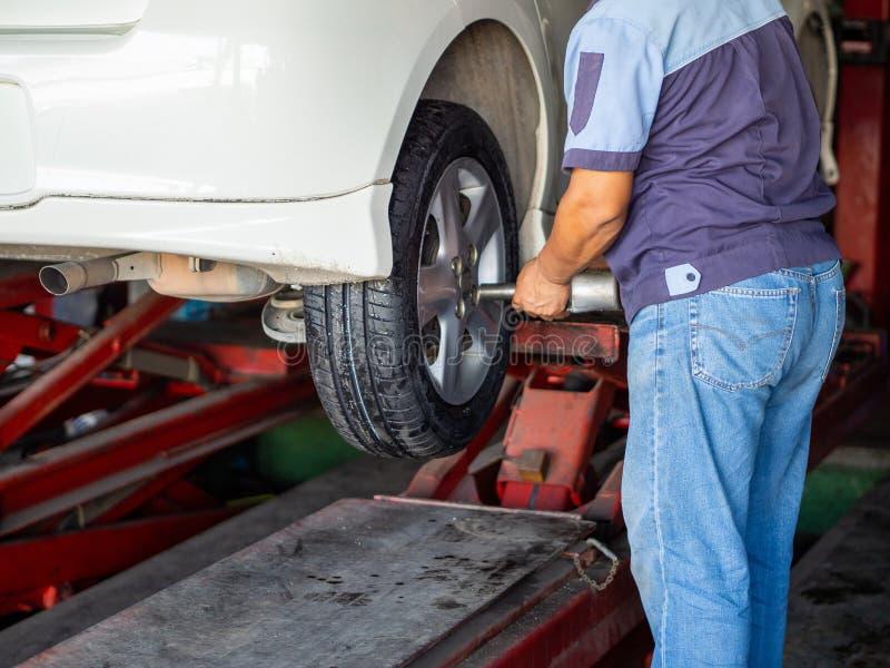 Mechanician veranderend autowiel in autoreparatiewerkplaats stock foto's