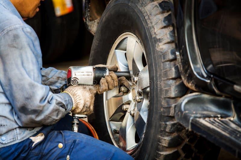 Mechanician veranderend autowiel in autoreparatiewerkplaats stock afbeeldingen