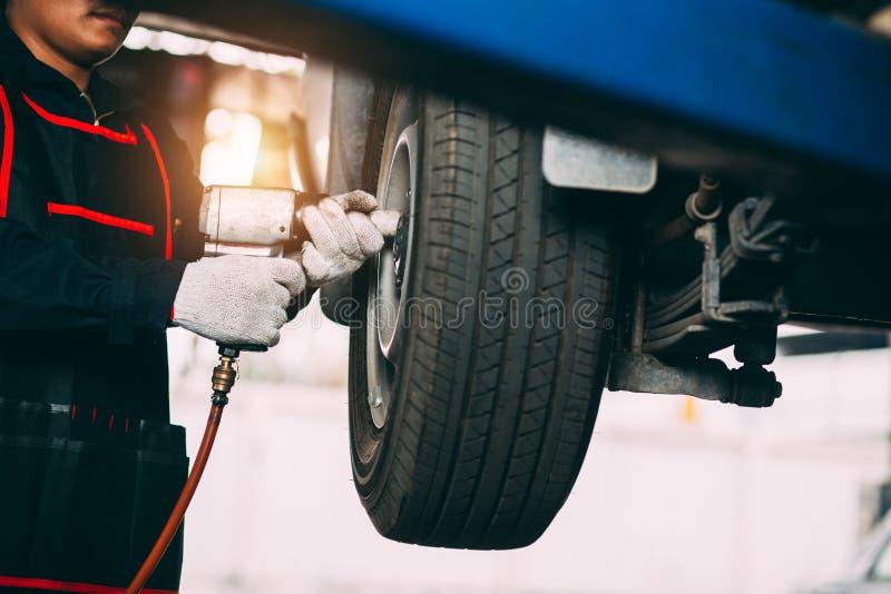 Mechanician zmienia? samochodowy toczy wewn?trz auto remontowego sklep zdjęcie stock