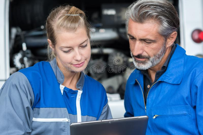 Mechanics checking information from tablet stock photo