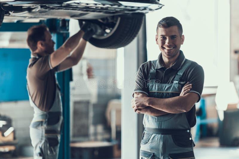 Mechanics Checking Wheel Bearings in Car Workshop. Two Caucasian Adult Technician Master in Uniform Repairing Car. Repairman Looking at Camera with Crossed stock images