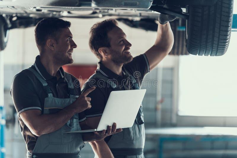 Two Mechanics Checking Wheel Bearings in Garage. Mechanics Checking Wheel Bearings in Car Workshop. Two Caucasian Adult Technician Master in Uniform Repairing stock photo