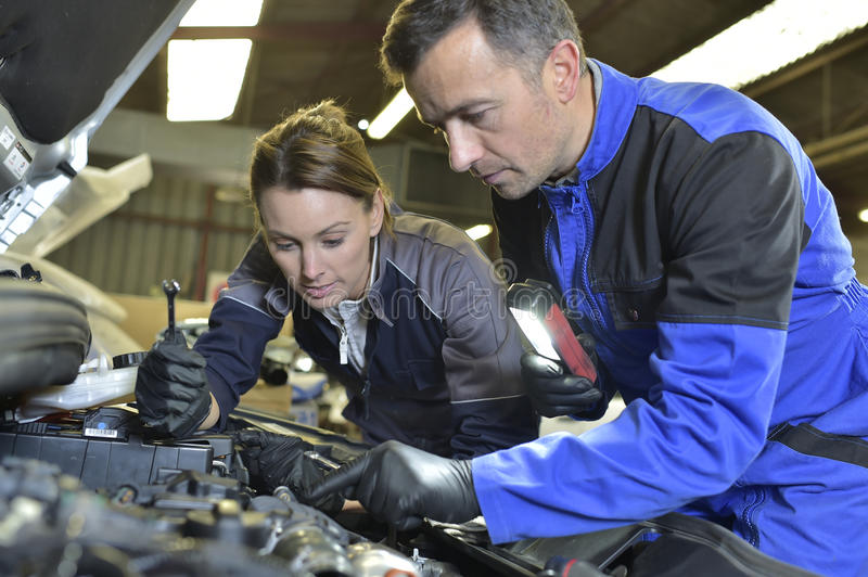 Mechanics instructor teaching apprentice royalty free stock photos