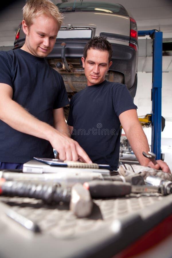 Mechanics Looking at Work Order. Two mechanics looking at work order and discussing repairs stock photos